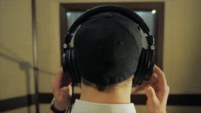 Mannen sätter på hörlurar i inspelningstudion arkivfilmer