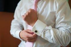 Mannen sätter på hans brudgum Accessories för skjortamanschettmorgonen Royaltyfri Bild