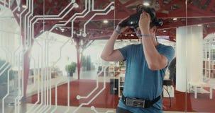 Mannen sätter på och tar av virtuell verklighetexponeringsglas arkivfilmer