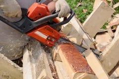 Mannen sågar trä med den orange chainsawen Arkivfoto