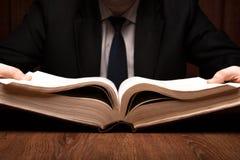 Mannen söker efter information i ordboken royaltyfria foton