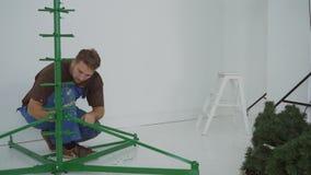 Mannen samlar den högväxta metallramen för en konstgjord julgran arkivfilmer