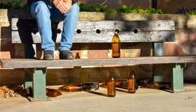 mannen satt på en bänk med många stora orange flaskor av öl som gjordes av exponeringsglas som fullständigt var tomt på, parkerar arkivbild