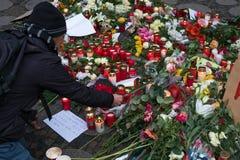 Mannen satta blommor och stearinljuset på jul marknadsför i Berlin Fotografering för Bildbyråer