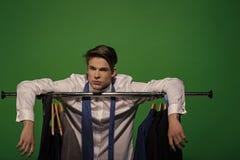 Mannen satte händer på kuggen med kläder i garderob Arkivbilder
