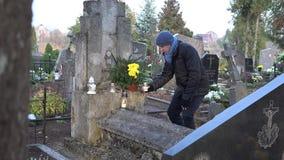 Mannen satte stearinljuset på grav efter frumoderförlust i kyrkogård 4K arkivfilmer