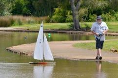 Mannen seglar fjärrkontroll som seglar träyachten Arkivfoton