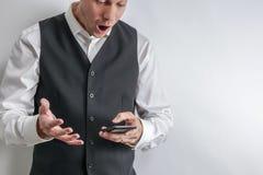 Mannen ser chockad, förvånat och att loooking på hans smarta telefon royaltyfria foton