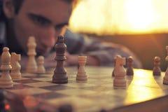 Mannen ser en schackbräde royaltyfria bilder