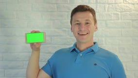 Mannen ser in i telefonen och en grön skärm arkivfilmer