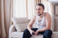 Mannen ser intressant överföring på TV:N Royaltyfri Fotografi