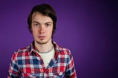 Mannen ser kameran barskt Stående av en allvarlig man i en plädskjorta på en purpurfärgad bakgrund, kopieringsutrymme Royaltyfri Foto