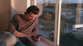 Mannen ser mobiltelefonen som bläddrar bandet i sociala nätverk som sitter på balkongen på solnedgången stock video