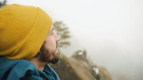 Mannen ser runt om honom anseende på överkanten av vagga i bergen som täckas med dimma lager videofilmer