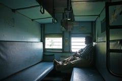 Mannen ser ut fönstret i en indisk järnvägplats för klassiker i en vagn för andra grupp i sen 2015 Arkivfoton