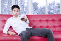 Mannen ser uttråkad hållande ögonen på tv hemma Royaltyfri Fotografi