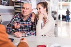 Mannen shoppar assistenten som arbetar med kunden i lager Fotografering för Bildbyråer