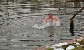 Mannen simmar i sjön i vinter Arkivbild