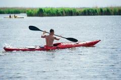 Mannen simmar på en röd kajak 01 Royaltyfria Bilder