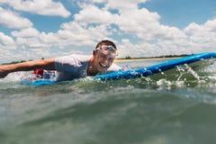 Mannen simmar på surfingbrädan i havet Fotografering för Bildbyråer