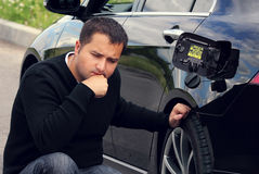 Mannen sitter bredvid bilen Royaltyfri Bild
