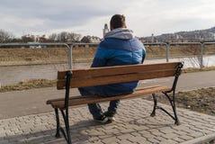 Mannen sitter i bänken royaltyfri fotografi