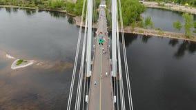 Mannen sitter i en Lotus position på ett rep som sträcks mellan servicen av bron på hög höjd Slackliner stock video