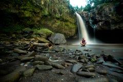 Mannen sitter korset som läggas benen på ryggen på, vaggar under vattenfallet royaltyfria foton