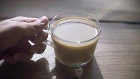 Mannen sitter med koppen kaffe på tabellen stock video
