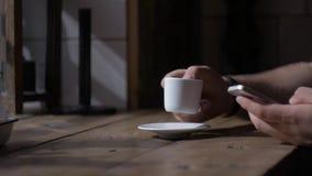 Mannen sitter med smartphonen på tabellen med koppen kaffe arkivfilmer