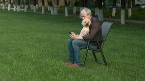 Mannen sitter med telefonen och innehavet en hund lager videofilmer