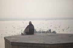 Mannen sitter nära havsfåglar och Ganges Arkivbilder