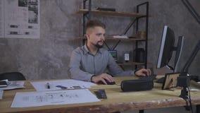 Mannen sitter ner på tabellen och startar att arbeta med datoren, bredvid teckningarna stock video