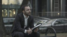 Mannen sitter på en bänk parkerar in och det missnöjda läs- affärsplanet royaltyfri foto