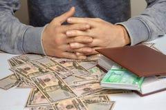 Mannen sitter på en tabell som överhopas med pengar Arkivfoto