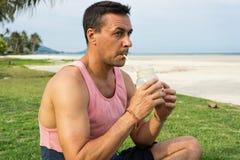 Mannen sitter på ett gräs i det tropiska landet av ön Samui, mandrinksmoothien Royaltyfria Bilder