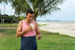 Mannen sitter på ett gräs i det tropiska landet av ön Samui, mandrinksmoothien Arkivbilder