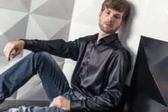 Mannen sitter på golvet fotografering för bildbyråer
