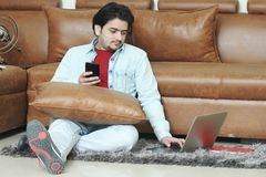 Mannen sitter på golvet med innehavtelefonen i hand och använder bärbara datorn fotografering för bildbyråer