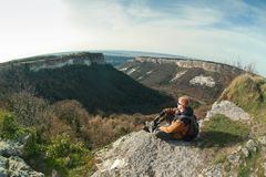 Mannen sitter på kanten av en klippa på den Mangup platån arkivfoto