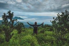 Mannen sitter på kullen och ser på den Batur vulkan i Bali arkivbild
