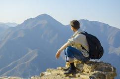 Mannen sitter på maximumet av berget och ser in i avståndet till bergen Arkivfoto