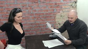 Mannen sitter på tabellen som intervjuar den unga kvinnan, tar av omslaget rollbesättning decollete stock video