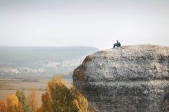 Mannen sitter p? ?verkanten av en klippa royaltyfri fotografi