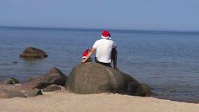 Mannen sitter vaggar på på sjösidan med den Santa Claus hatten stock video