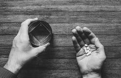 Mannen ska äta preventivpillerar och kapslar och taget med vatten, svarta vita foto Arkivbilder