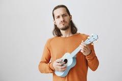 Mannen ska vagga dig med hans musikerexpertis Stående av den säkra stiliga grabben i hållande ukulele för orange tröja som drar arkivfoton