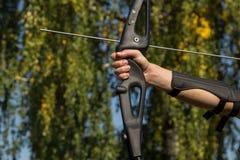 Mannen skjuter från pilbågen Närbild Övning av bågskytte royaltyfria foton
