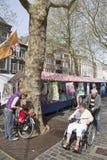 Mannen skjuter kvinnan i rullstol längs marknad i holland Arkivfoto
