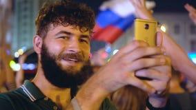 Mannen skjuter mobiltelefonen, som folket jublar i seger av Ryssland på fotboll arkivfilmer